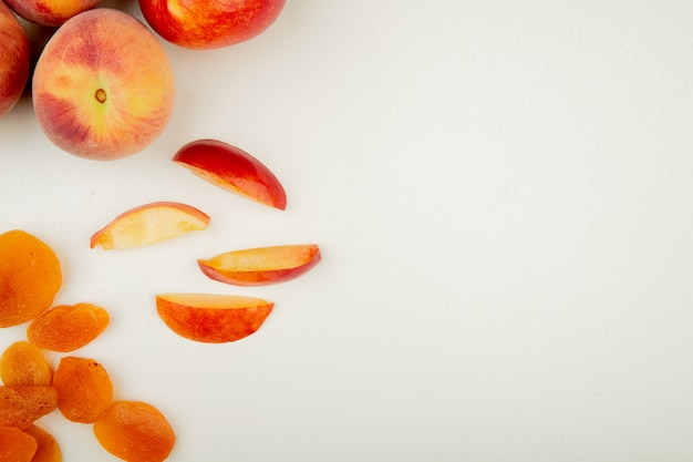 Top view of whole and sliced peaches and yellow raisins on left side and white surface with copy space