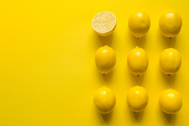 Top view whole and sliced ripe lemon laid out in several rows on a yellow surface, concept of health and vitamins