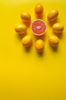 Top view whole and sliced ripe lemons and grapefruit laid out in the shape of a dial on a yellow surface, concept of health and vitamins