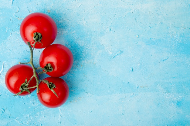 Top view of whole tomatoes on left side on blue surface