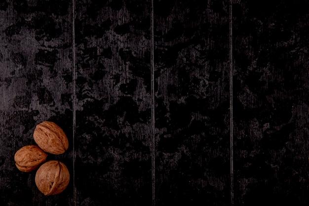Vista dall'alto di intere noci su fondo di legno nero con spazio di copia