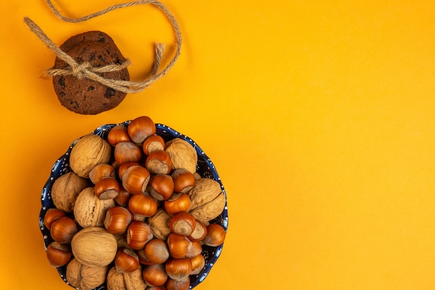 Top view of whole walnuts and hazelnuts in a bowl and oatmeal cookies tied with rope on yellow