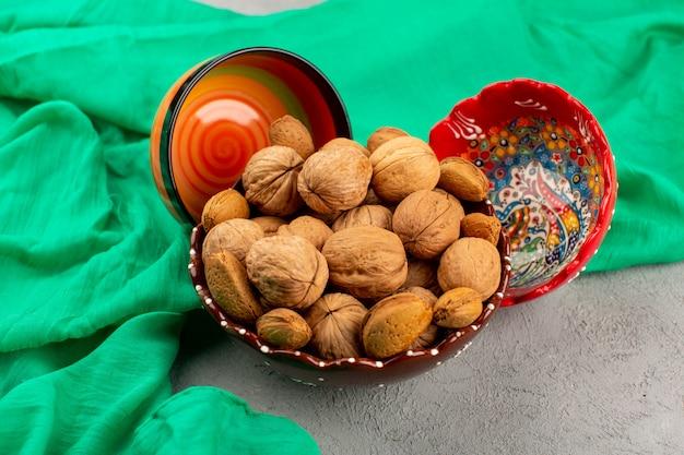 Вид сверху целые грецкие орехи внутри тарелки