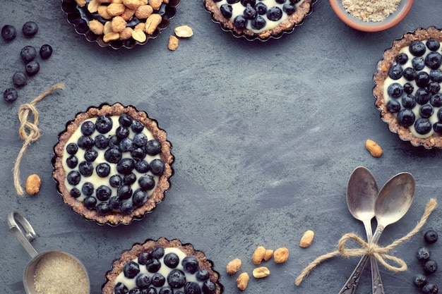Top view on wholegrain blueberry tarts with vanilla cream