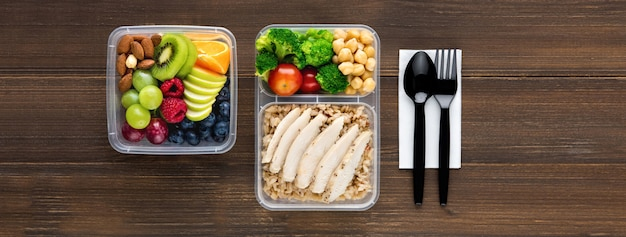 Top view of wholesome nutrient rich food set in take away boxes with spoon and fork on wood table banner background