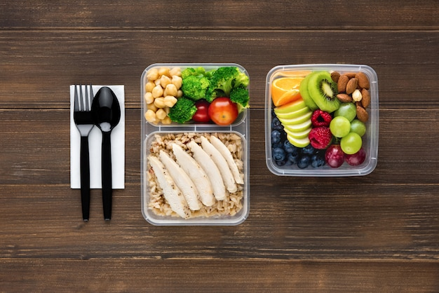 Top view of wholesome nutrient rich food set in take away boxes with spoon and fork on wood table ready to eat