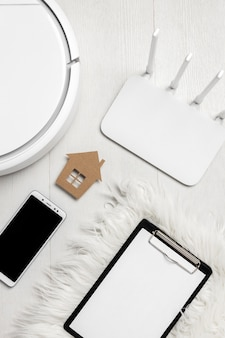 Top view of wi-fi router with smart devices and house figurine