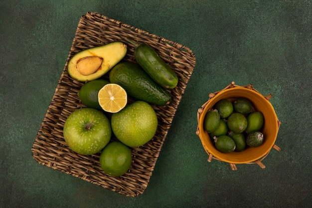 Top view of a wicker tray of fresh foods such as green apples limes avocado and cucumber with feijoas on a bucket on a green background