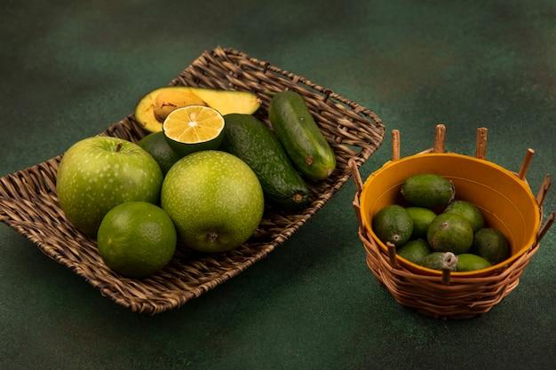 Vista dall'alto di un vassoio di vimini di cibi sani come mele verdi limette avocado e cetrioli con feijoas su un secchio su una superficie verde