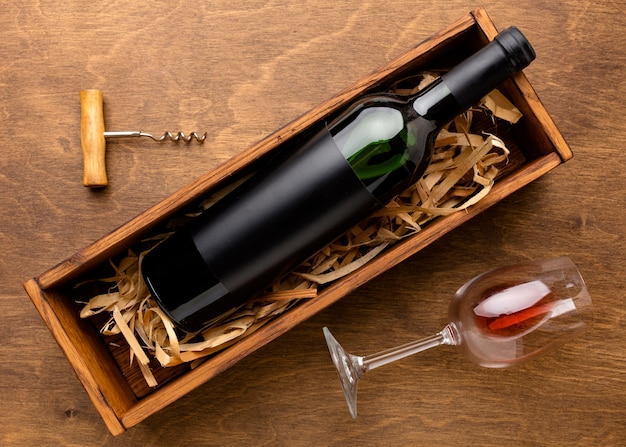 Top view wine bottle and glass with corkscrew