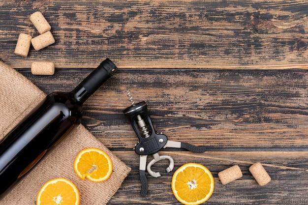 Bottiglia di vino di vista superiore su tela di sacco con lo spazio della copia sull'orizzontale di legno scuro