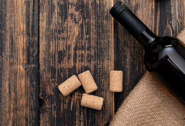 Top view wine bottle on sackcloth with copy space on dark wooden  horizontal