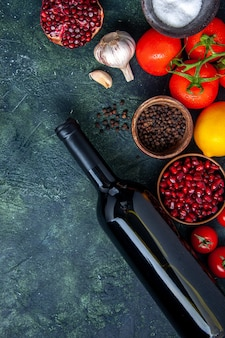 Top view wine bottle tomatoes garlic pomegranate different spices in small bowls on table