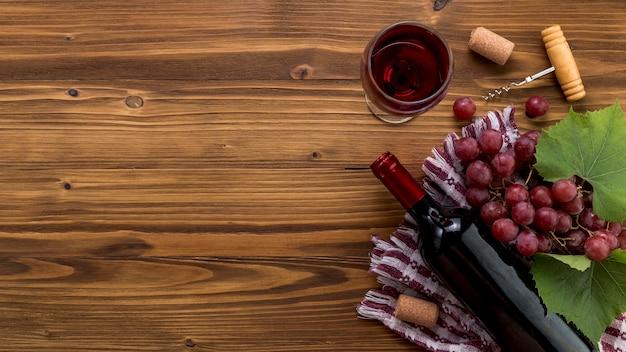 Вид сверху бутылка вина с бокалом на деревянном фоне