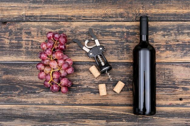 暗い木製の水平のブドウの上から見るワインボトル