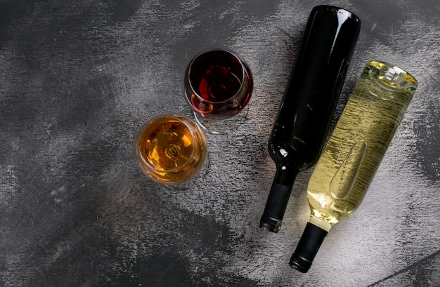 Top view wine bottles with glasses and copy space on black stone  horizontal