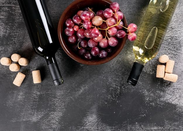 Bottiglie di vino di vista superiore con l'uva e lo spazio della copia sull'orizzontale di pietra nero