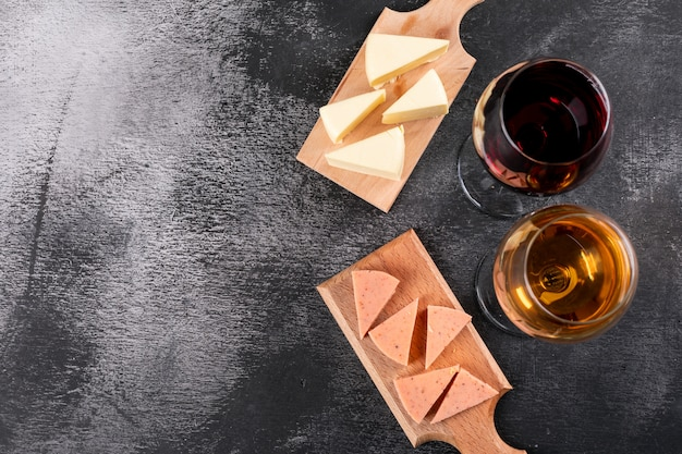 Top view of wine glasses and cheese on wooden cutting board and copy space on dark background horizontal