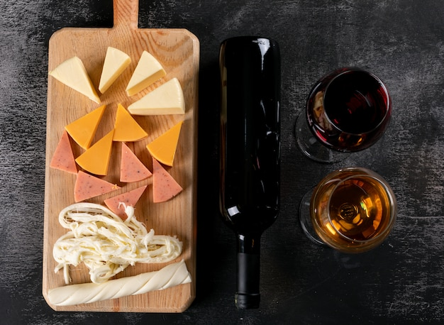Top view of wine glasses and cheese on wooden cutting board on dark  horizontal