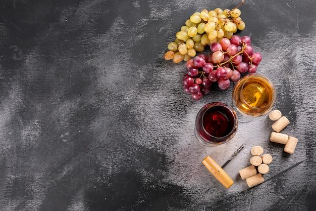 Vetri di vino di vista superiore con l'uva e lo spazio della copia sull'orizzontale di pietra nero