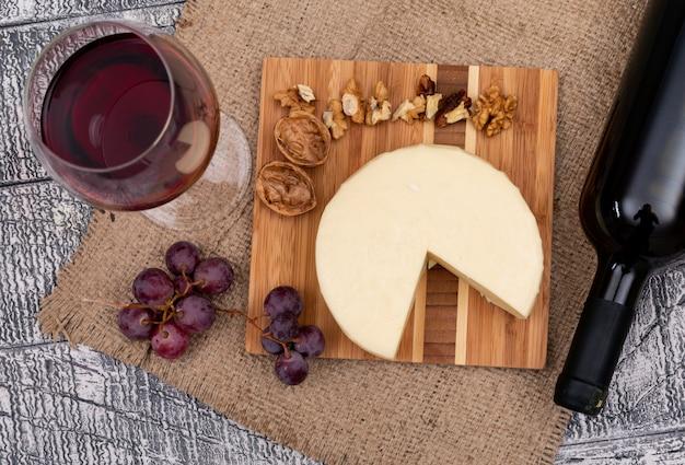 Vino di vista superiore con l'uva e il formaggio a bordo e sull'orizzontale di legno bianco