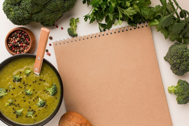 Vista dall'alto della zuppa di broccoli invernale in una ciotola con il taccuino