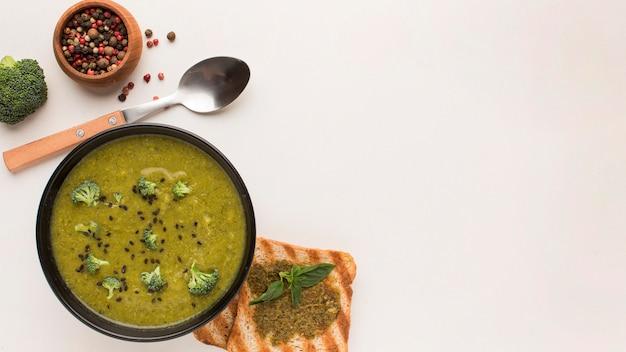 Vista dall'alto della zuppa di broccoli invernali nella ciotola con pane tostato e copia spazio
