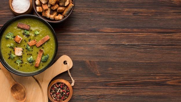 Vista dall'alto della zuppa di broccoli invernale con crostini di pane e copia spazio