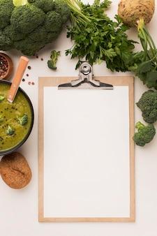 Vista dall'alto della zuppa di broccoli invernali con blocco note e sedano