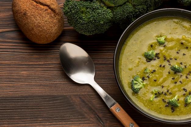 Vista dall'alto della zuppa di broccoli invernali con cucchiaio e pane