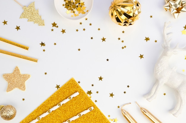 Top view winter christmas frame made of golden xmas tree decorations on a white table background