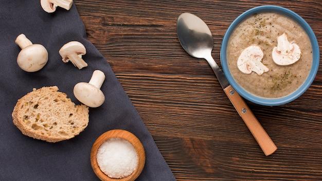 Vista dall'alto della zuppa di funghi invernali in una ciotola con cucchiaio e pane