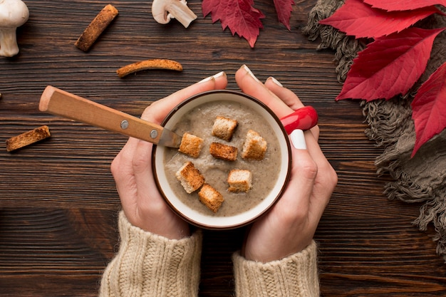 Top view of winter mushroom soup in mug held by hands with croutons and spoon