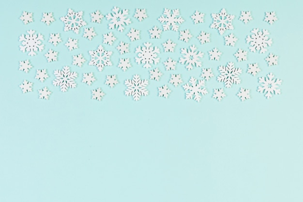 Top view of winter ornament made of white snowflakes on colorful surface
