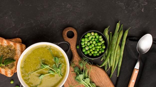 Vista dall'alto della zuppa di piselli invernali nella ciotola con pane tostato e cucchiaio