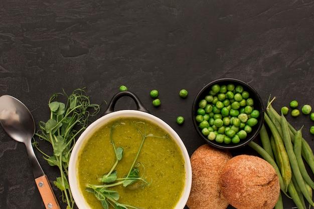 Vista dall'alto della zuppa di piselli invernali con pane e copia spazio