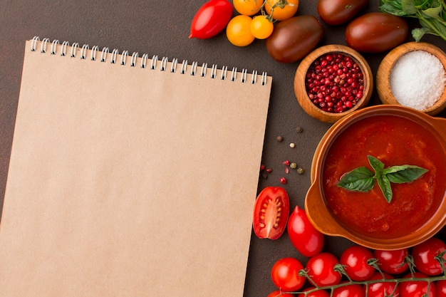 Top view of winter tomato soup in bowl with notebook