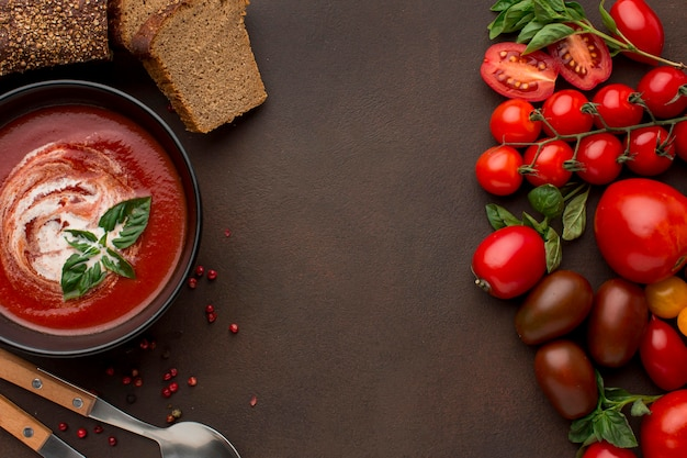 Top view of winter tomato soup in bowl with toast and spoons