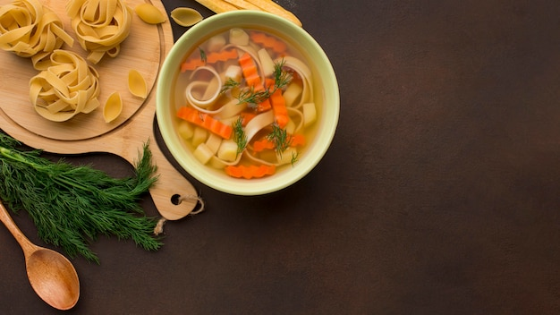 Top view of winter vegetables soup in bowl with copy space and tagliatelle