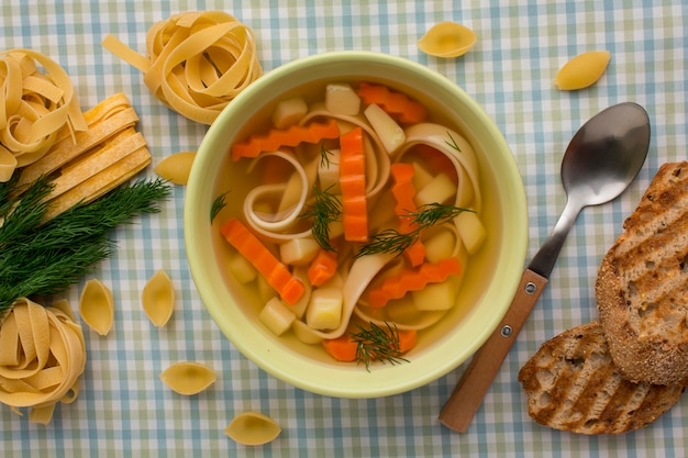 Top view of winter vegetables soup in bowl with spoon and tagliatelle