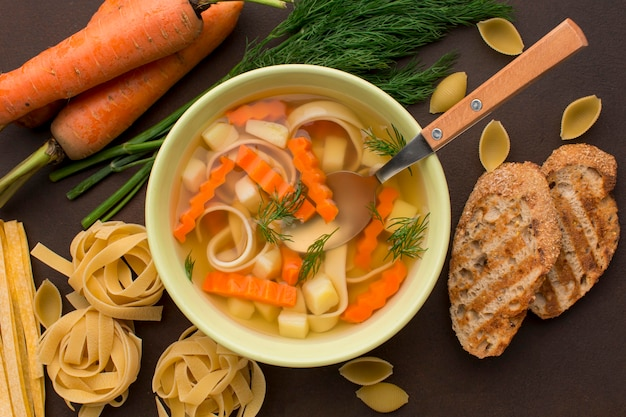 Top view of winter vegetables soup in bowl with spoon and toast