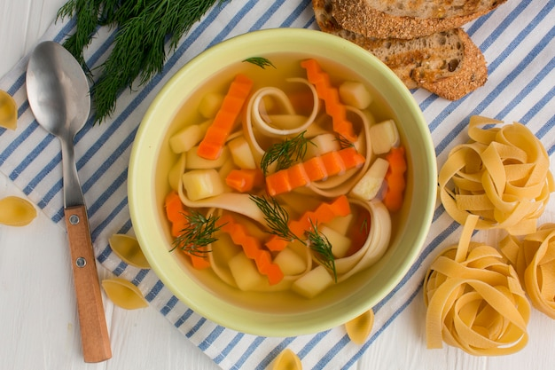 Top view of winter vegetables soup in bowl with tagliatelle and toast