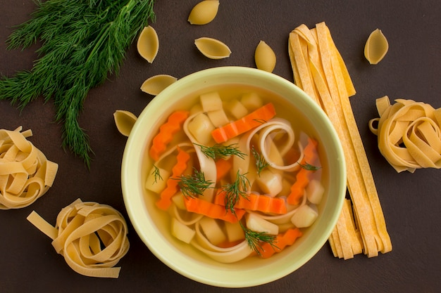 Top view of winter vegetables soup in bowl with tagliatelle