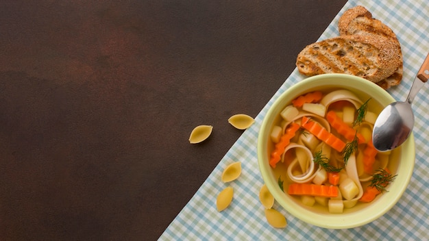Top view of winter vegetables soup in bowl with toast and copy space