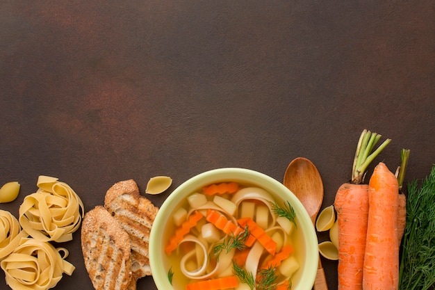Top view of winter vegetables soup in bowl with toast and tagliatelle