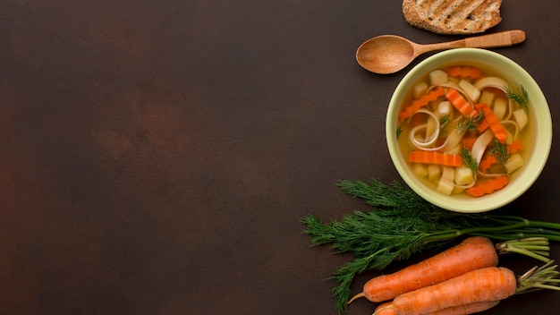 Top view of winter vegetables soup with carrots in bowl and copy space