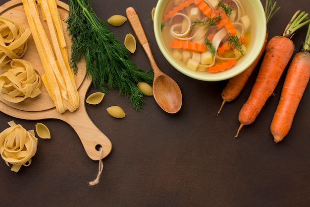 Top view of winter vegetables soup with carrots and tagliatelle