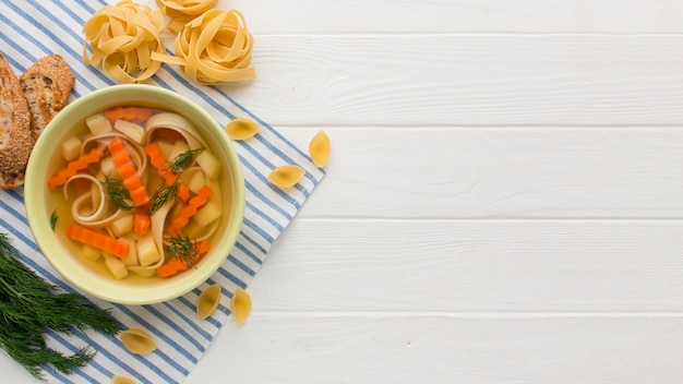Top view of winter vegetables soup with copy space and tagliatelle
