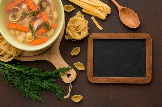 Top view of winter vegetables soup with tagliatelle and blackboard