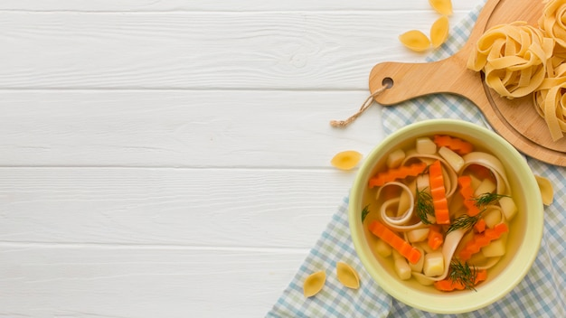 Top view of winter vegetables soup with tagliatelle and copy space